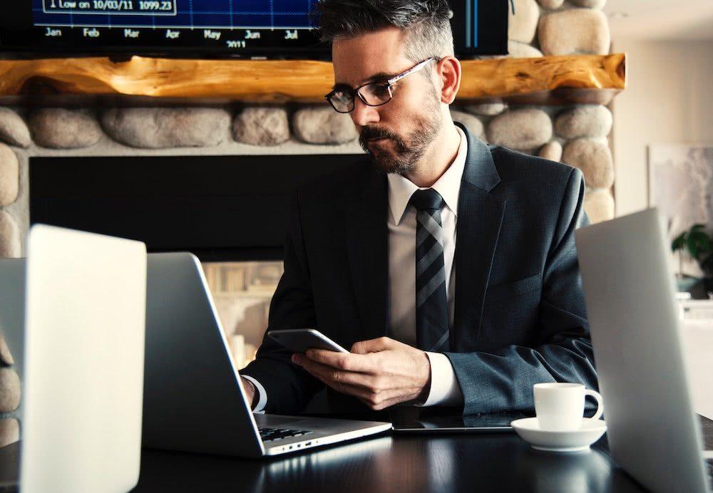Carreira no mercado financeiro - homem com notebook e celular